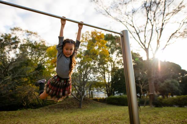 girl playing with iron bar - horizontal bar stock photos and pictures