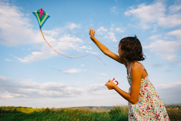 Girl playing with kite in field stock photo