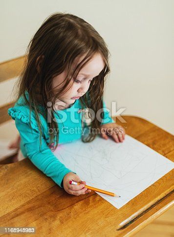 A two year old girl makes scribbles on paper, seated in a vintage school desk.