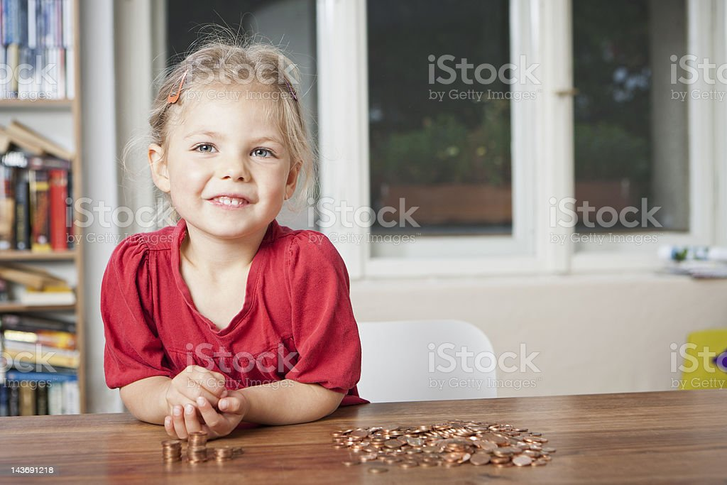 Girl playing with pennies at table stock photo