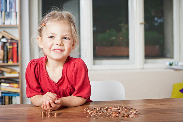 Girl playing with pennies at table  allowance stock pictures, royalty-free photos & images