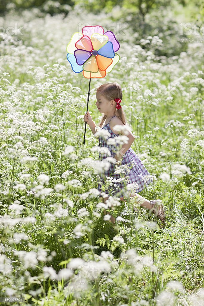 Girl playing with pinwheel in field of flowers royalty-free stock photo
