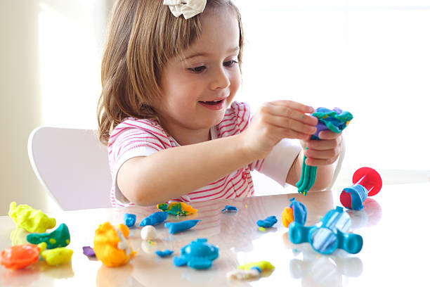 Girl playing with play dough stock photo