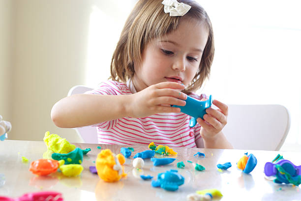 mädchen spielt mit spielen teig - knete spiele stock-fotos und bilder