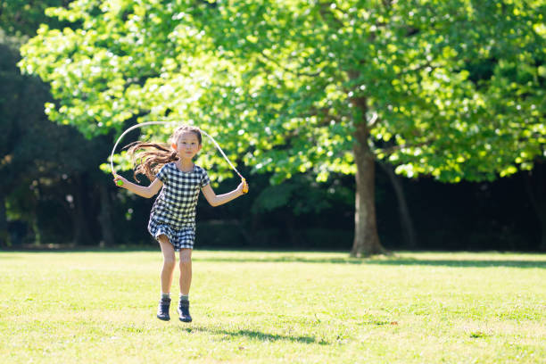 Girl playing with skipping rope stock photo
