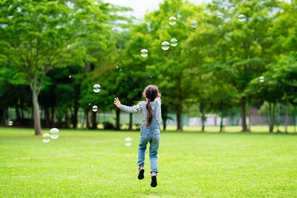 石鹸の泡で遊んでいる女の子 - people of color ストックフォトと画像