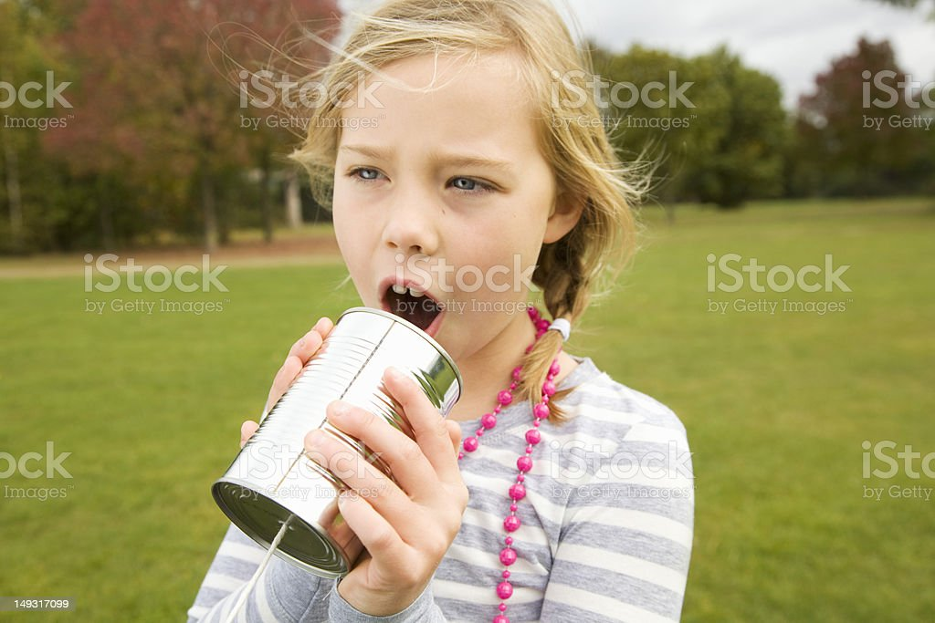 Girl playing with tin can telephone royalty-free stock photo