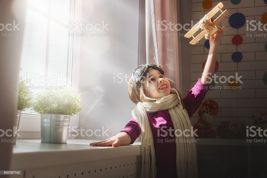 girl playing with toy airplane stock photo