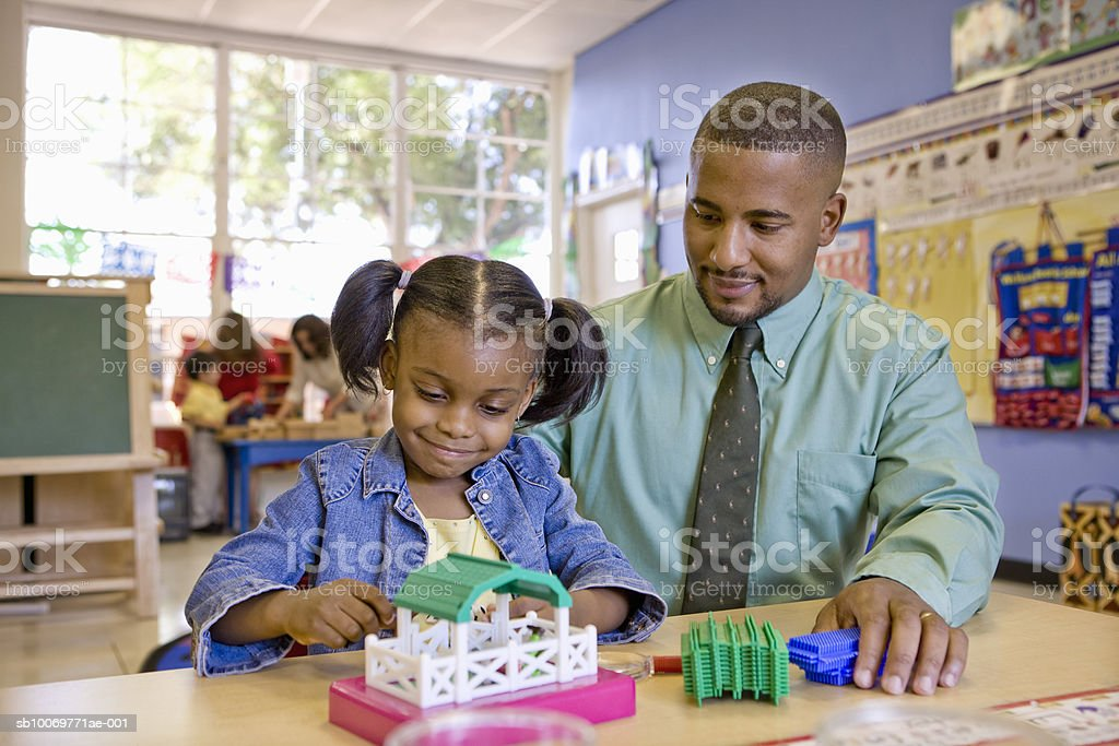 Girl (4-5) playing with toy beside father foto de stock libre de derechos