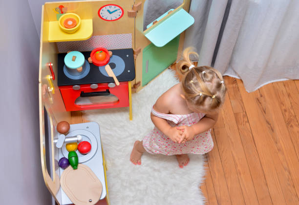 Girl playing with toy on a kitchen stock photo