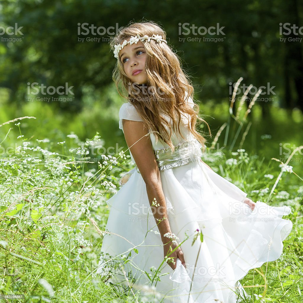 Girl playing with white dress in field. stock photo