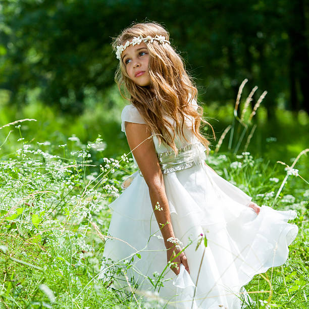 girl playing with white dress in field. - communion stock photos and pictures