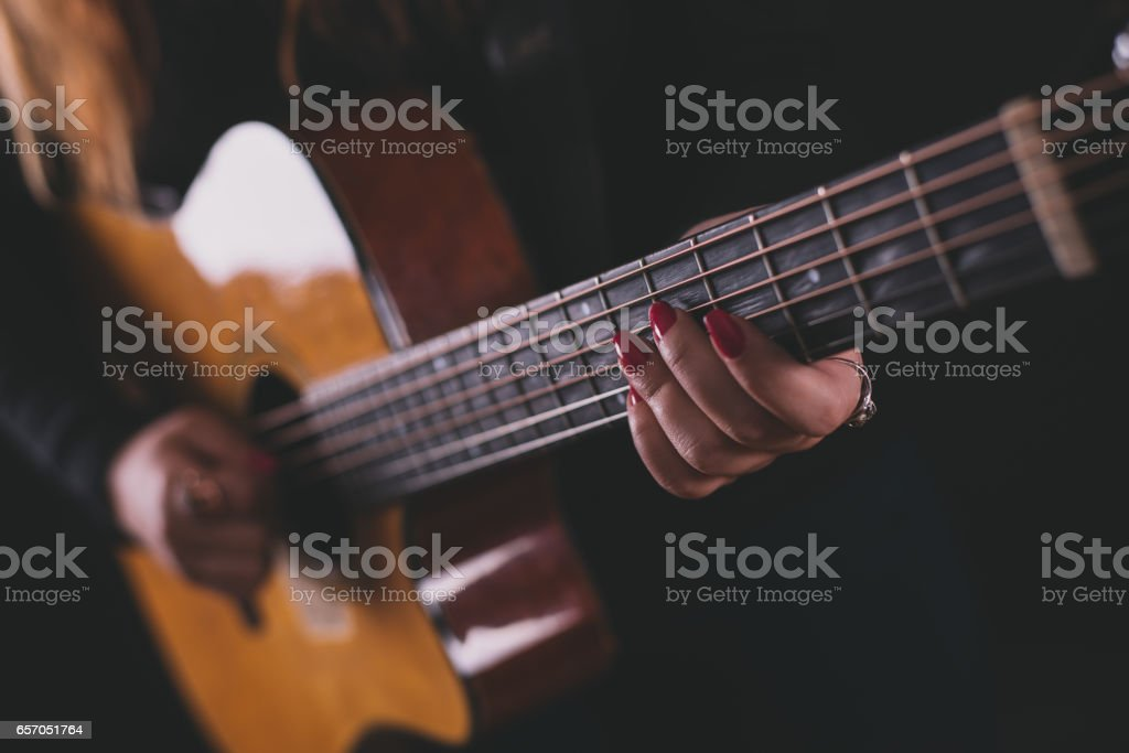 Girl plays acoustic guitar stock photo