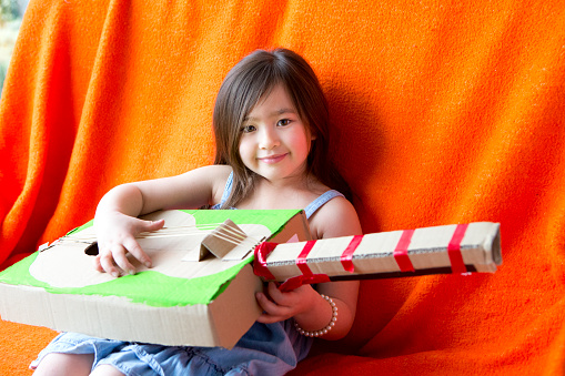 Chinese girl sits relaxing playing a homemade guitar. She is sitting against an orange throw and smiling at the camera. The guitar is made out of cardboard, tape and string.