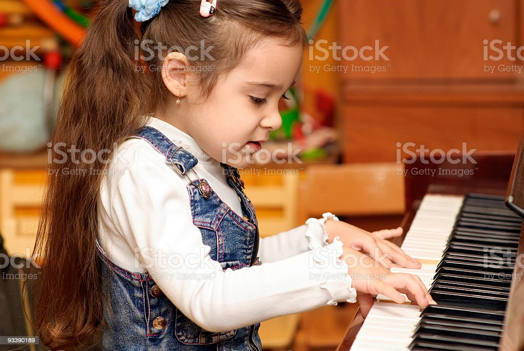 Girl plays piano royalty-free stock photo