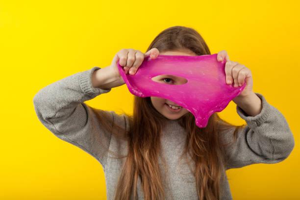 Niña juega con limo sobre fondo amarillo, retrato. Experimentos divertidos - foto de stock
