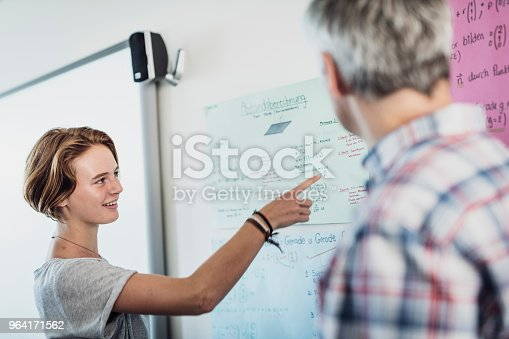Teenage student pointing at document while standing with teacher. She is smiling while learning in classroom. Confident female is giving presentation in school.