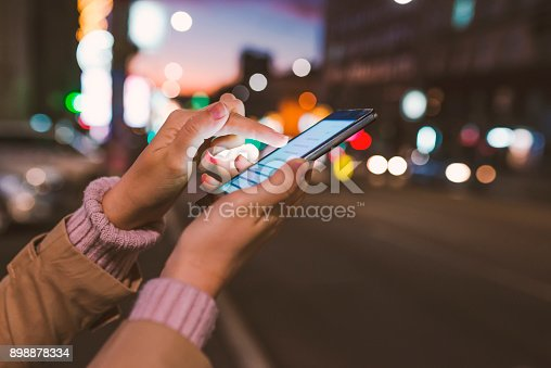 istock Girl pointing finger on screen smart phone on background illumination color light in night city 898878334