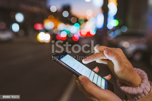 621574390 istock photo Girl pointing finger on screen smartphone on background illumination bokeh color light in night atmospheric city 898878320