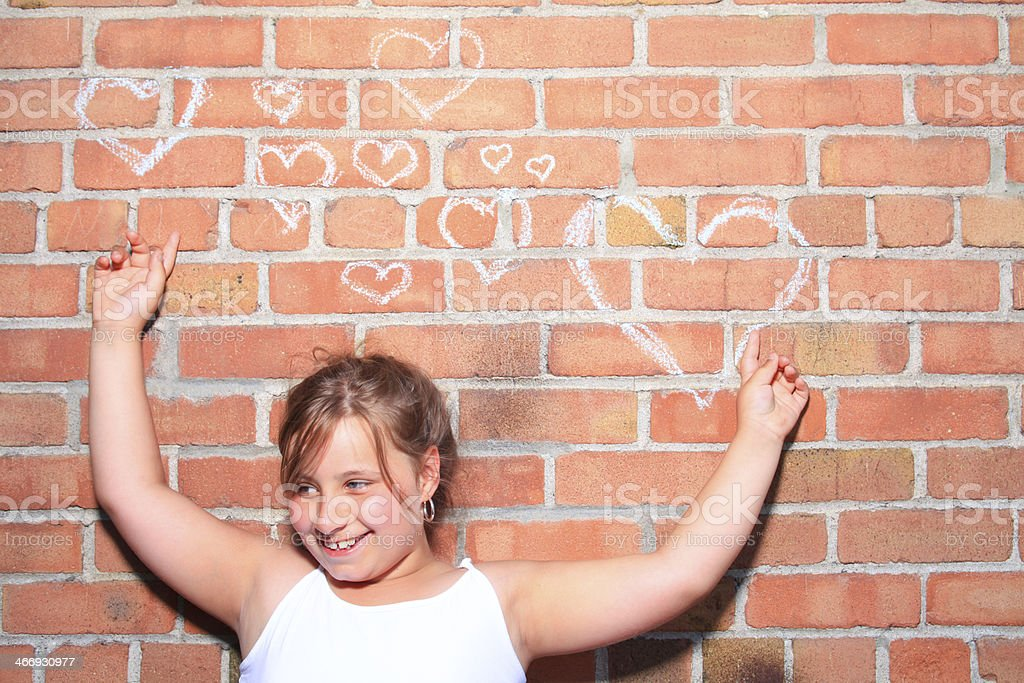 Girl Pointing Love Heart Brick Smile stock photo