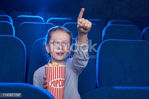istock Girl pointing with finger at screen in cinema. 1147577707