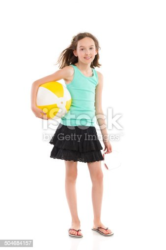 Girl in green shirt and black skirt standing and holdng a beach ball under her arm. Full length studio shot isolated on white.