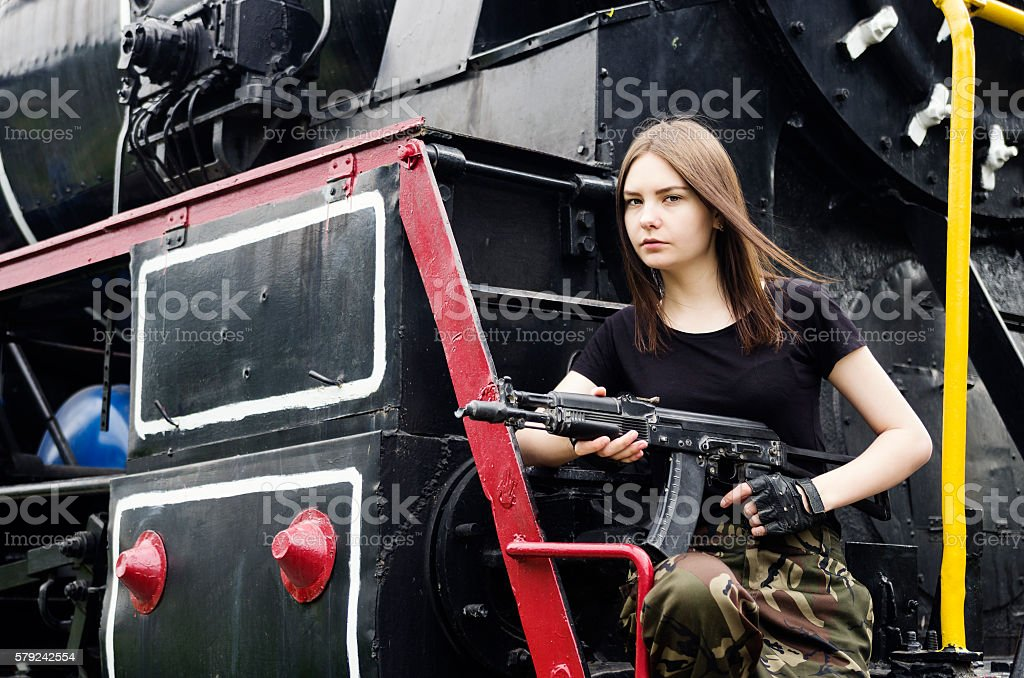 Girl posing with a gun next to the engine stock photo