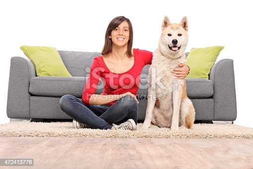 istock Girl posing with her dog seated by a couch 472413776