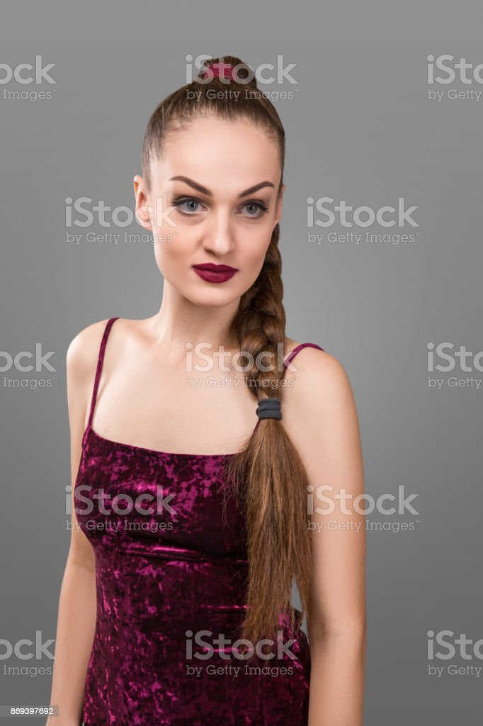 Girl posing with pigtail in a studio on gray background stock photo