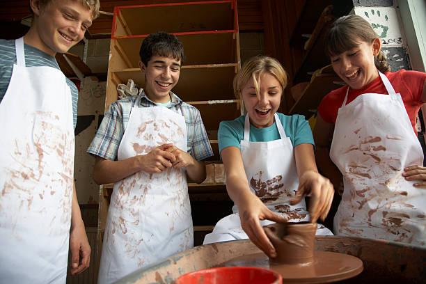 Girl (13-15) potting on wheel surrounded by classmates, smiling stock photo