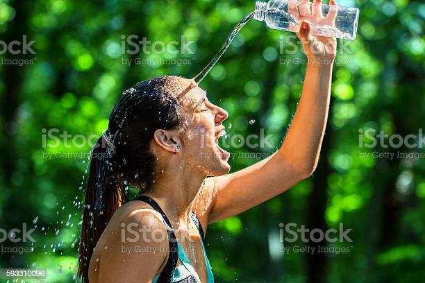 Photo of Girl pouring water on face after workout.