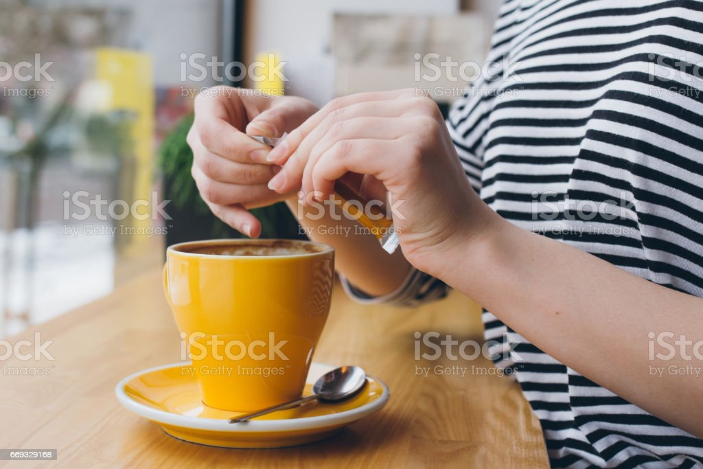 Girl pours sugar from a bag into a mug of coffee stock photo