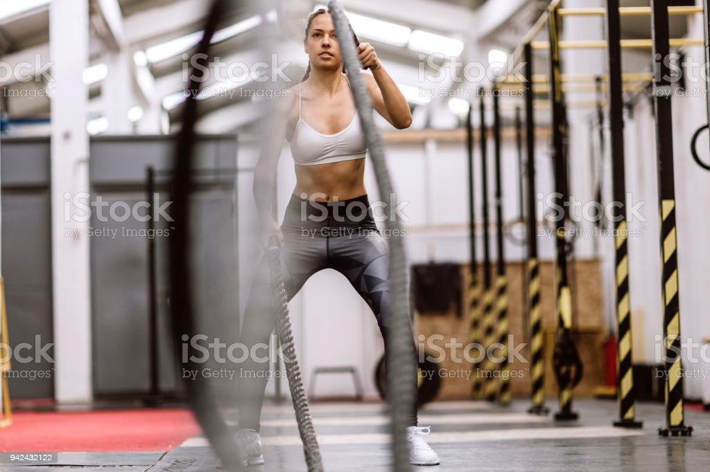 Girl Power On Rope In Gym stock photo