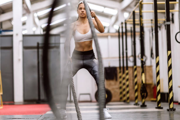 girl power on rope in gym - battle stock photos and pictures
