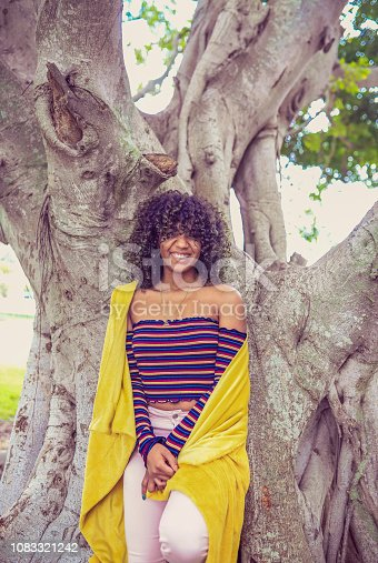 Beautiful african american woman with big natural hair stands under a large banyan tree in a park. She is wrapped in a blanket in millenial yellow. She is a beauty, and smiling and happy. Outdoors in a chilly setting. Retro styling and vintage feel, photo, model and styling feels like an image from the 1970's but  she could be from any decade. She is clearly a confident young woman
