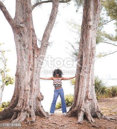 Beautiful african american woman with big natural hair stands between two trees with arms reached out extended trunk to trunk. She exudes an aura of power, fierceness, and confidence. Her outfit is retro and she could be from any decade. She is clearly a force