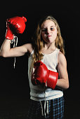 Young girl with black eye and boxing gloves.