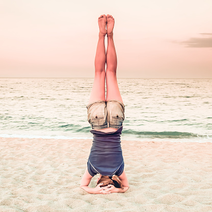 girl practice yoga headstand on the beach inverted posture