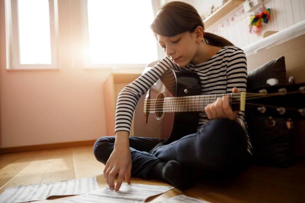 mädchen üben gitarre zu hause - one song training stock-fotos und bilder