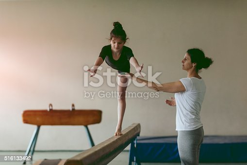 Cute Little Girl Practicing gymnastics with her coach. She is her mother and coach. Mother preparing her daughter for new championship. Exercise in a school gym. She is determined to success.