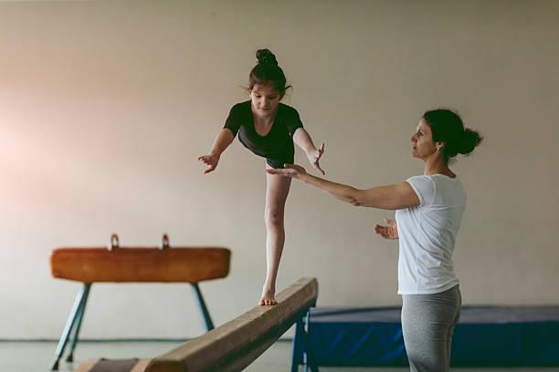 girl practicing gymnastics - balance beam stock photos and pictures