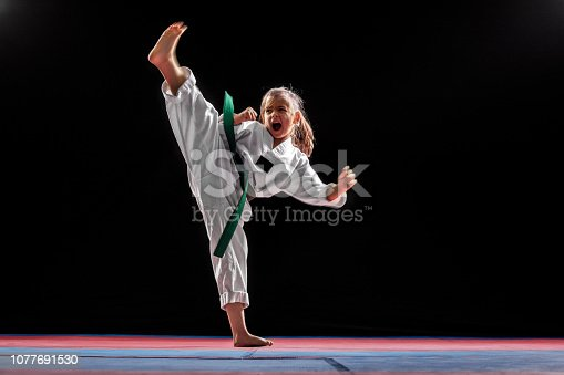 Young girl practicing taekwondo high kick in the air. Taekwondo is one of the most popular martial arts. She is working in gym with dark background
