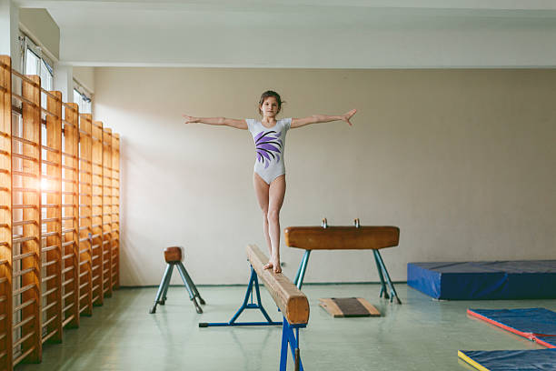 girl practicing on gymnastics beam. - balance beam stock photos and pictures
