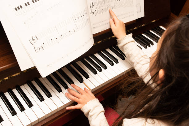Girl practicing the piano stock photo