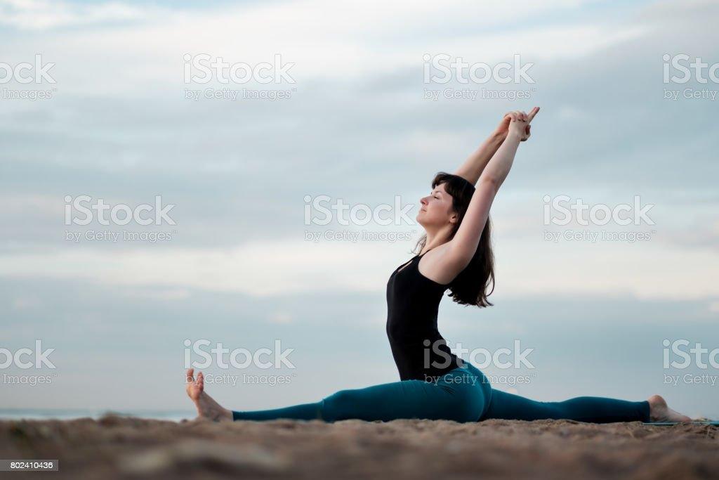 Girl practicing yoga in nature hanumanasana monkey pose. stock photo