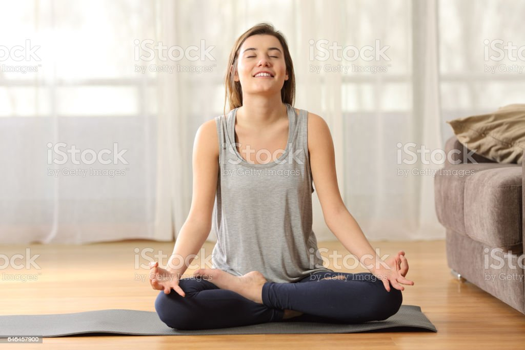 Girl practicing yoga on the floor at home stock photo