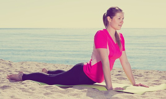 Girl Practicing Yoga Poses On Beach Stock Photo - Download Image Now