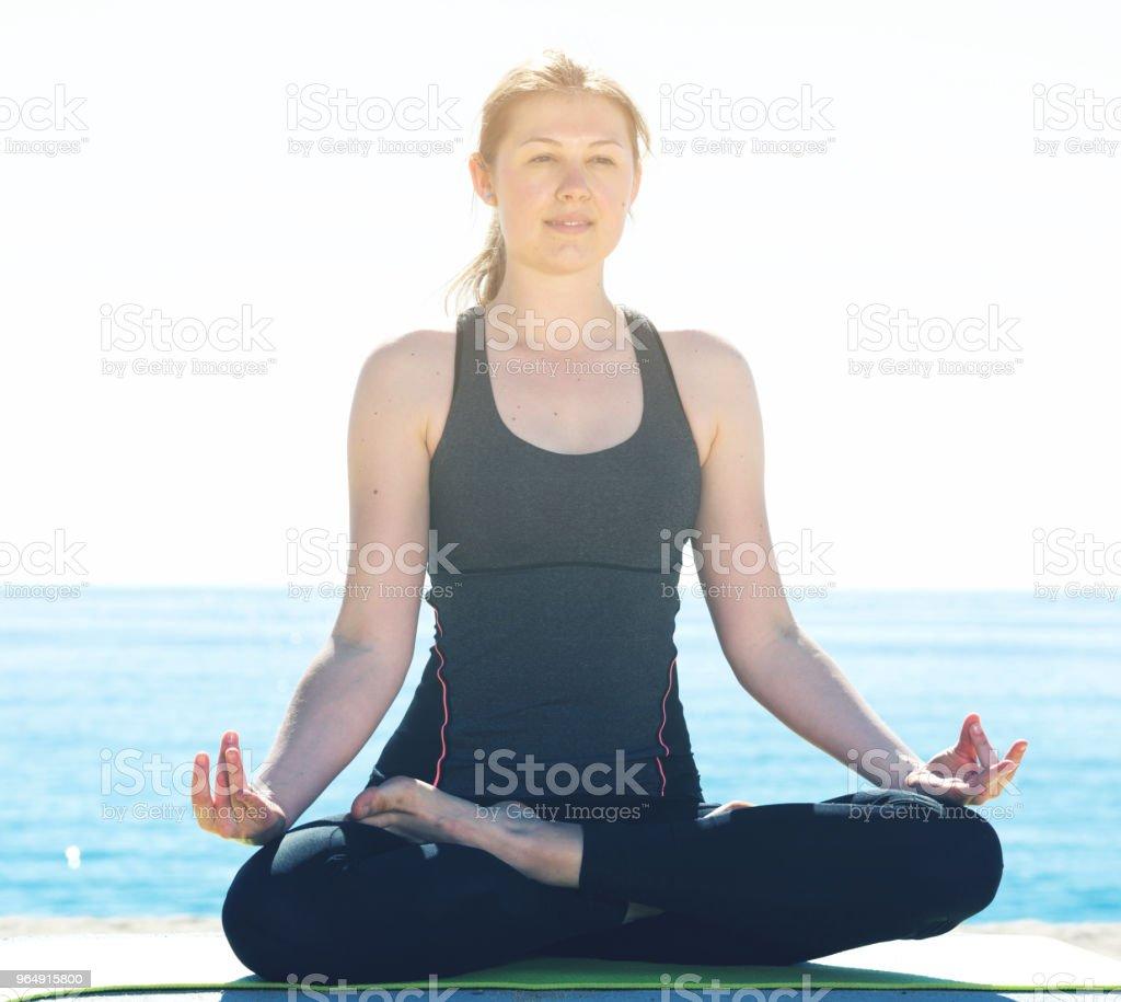練習瑜伽姿勢在海灘上的女孩 - 免版稅享受圖庫照片