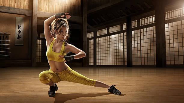 chica practicando artes marciales en dojo - artes marciales fotografías e imágenes de stock