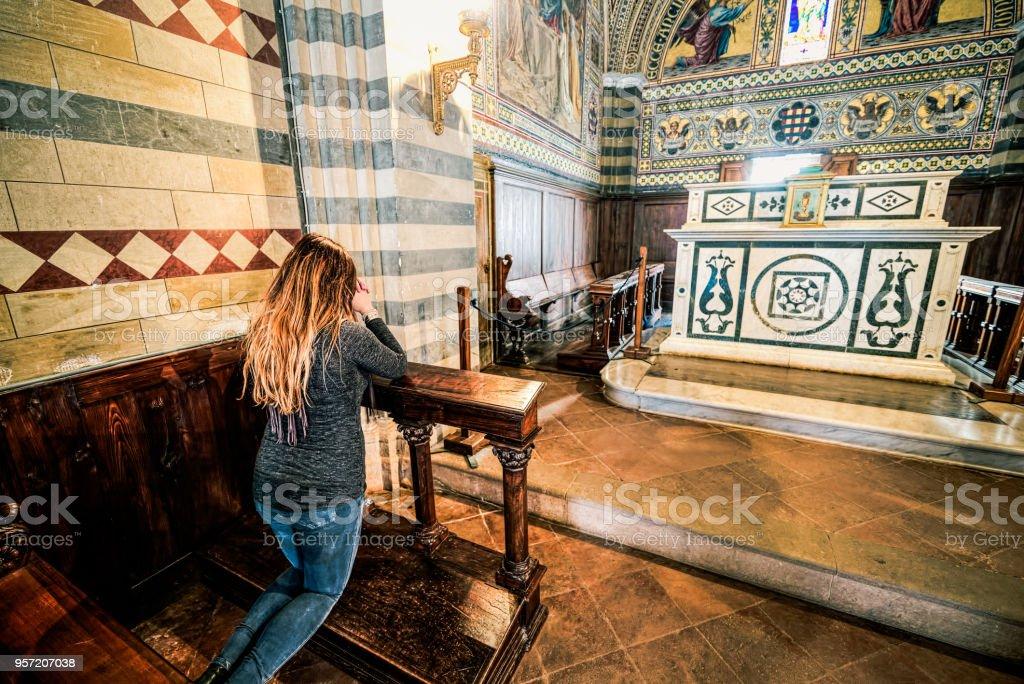 Menina a rezar de joelhos em uma igreja, religiosos sujeitos - foto de acervo